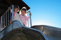 Twins on a bent slide. Twins standing at the top on a bent slide, sun comming from behind - back lightning Royalty Free Stock Image