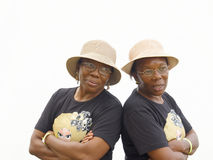 Twins in black. Identical twin sisters in hats and black T-shirts Royalty Free Stock Images