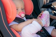 Twins boy and girl in child seats in the car. Safety transportation for babies. Children up to a year.
