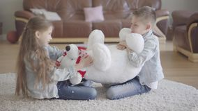 Twins boy and girl sit in living room on the floor and dont know how to share between them a big taddy bear. Kids stock video