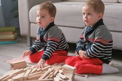 Twins boys brothers are building from wooden blocks sitting on the floor by the sofa in their room. Twins boys are building from wooden blocks sitting on the royalty free stock photo