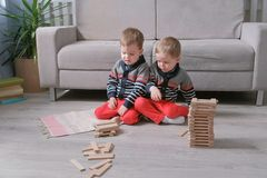 Twins boys brothers are building from wooden blocks sitting on the floor by the sofa in their room. Twins boys are building from wooden blocks sitting on the royalty free stock photos