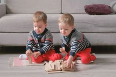 Twins boys brothers are building from wooden blocks sitting on the floor by the sofa in their room. royalty free stock photography