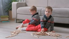 Twins boys brothers are building a tower from wooden blocks sitting on the floor by the sofa in their room. Twins boys are building from wooden blocks sitting stock video