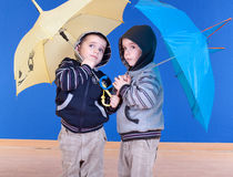Twins brother  have fun under an umbrellas Stock Images