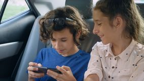 Twins brother and sister use the phone while traveling in the car.  royalty free stock photography