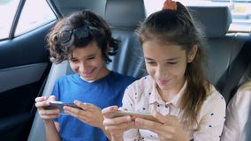 Twins brother and sister use the phone while traveling in the car.  stock photo