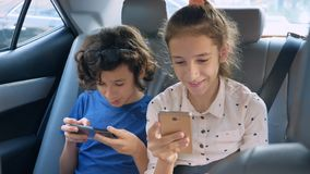 Twins brother and sister use the phone while traveling in the car.  royalty free stock photos
