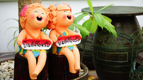 Twins ceramic figures hold boards say Stock Photo