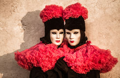 Twins couple with black and red costume during venice carnival Royalty Free Stock Images