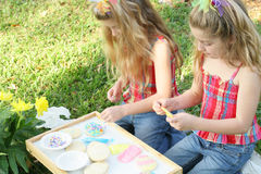 Twins decorating cookies outside. Shot of twins decorating cookies outside Royalty Free Stock Photo