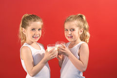 Twins drinking milk smile. Shot of twins drinking milk smile Royalty Free Stock Photo