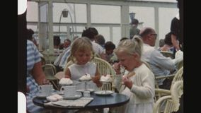 Twins eating ice cream. Netherlands, Noordwijk, Summer 1956. Two little blonde girls, twins, dressed in white, sit at a table and enjoy eating ice cream in a stock video