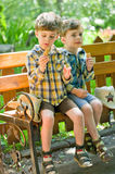 Twins eating ice cream. Three year old identical twins eating ice cream in the park. Children dressed in the colours of the Ukrainian flag. On the hat of one of Stock Image