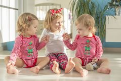Twins and elder sister sitting at home stock images