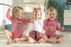 Twins and elder sister sitting at home stock image
