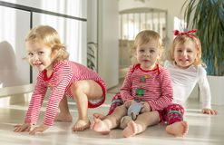 Twins and elder sister sitting at home stock photo