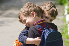 Twins embrace each other to hug. Identical twins embrace each other in hug. They are smiling. Boys are curly-headed. The weather is bright. They are in different Stock Image