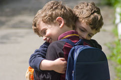 Twins embrace each other to hug. Identical twins embrace each other in hug. They are smiling. Boys are curly-headed. The weather is bright. They are in different Royalty Free Stock Images