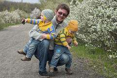 Twins with father. Identical twins with their father on the gravel road near the blossoming shrubs. Season - spring. Boys dressed in the same stripy jumpers and Stock Image