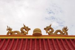 Twins foam crafting dragon with marble in the middle on top of red roof. Twins yellow foam crafting dragon with marble in the middle on top of red roof Stock Images