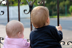 Twins at the gate. Boy and Girl from behind standing at a gate and awaiting someone/something Royalty Free Stock Photography