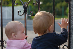 Twins at gate waving hand Stock Images