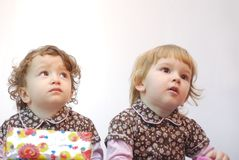 Twins with gift. Twin sisters with gift looking up Stock Photo
