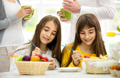 Twins girls decorating Easter eggs Royalty Free Stock Photography