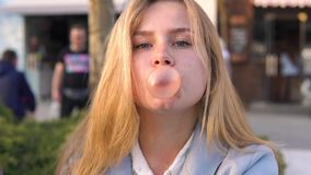 Twins girls friends having fun on evening broadway and Chewing bubble gum. The sister ruined a gum bubble stock footage