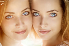 Twins. A group of young beautiful girls. Two women face close-up Royalty Free Stock Photos