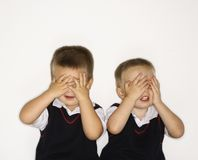 Twins with hands over eyes. Caucasian male children twins with hands over eyes royalty free stock image