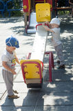 Twins have fan with swing. Two year old identical twin boys have fan with swing on the playground. Children are dressed in the same clothes with caps in Stock Photography