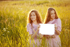 Twins holding white blank poster  outdoors Stock Photos