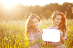 Twins holding white blank poster  outdoors Stock Photography
