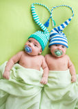 Twins infant boys babies weared in striped hats tied by heart. royalty free stock image