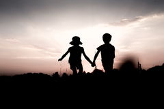 Twins jump off a hill holding hands at sunset. Silhouettes of kids jumping off a hill at sunset. Little boy and girl jump high holding hands. Brother and sister royalty free stock image