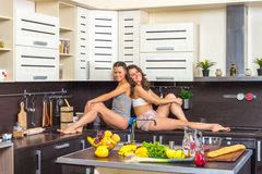 Twins in kitchen Stock Photo