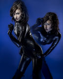 Twins in latex costume, brunette Stock Images