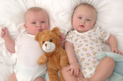 Twins lying with their teddy bear Stock Images