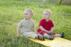 Twins on the meadow. Identical twins sit on the mat in the meadow. Children are dressed in the same clothes in different colors - beige and red. Season - summer Stock Images