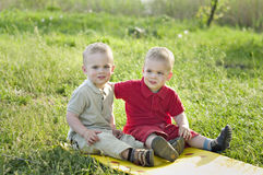 Twins on the meadow. Identical twins sit on the mat in the meadow. Children are dressed in the same clothes in different colors - beige and red. Season - summer Royalty Free Stock Photos