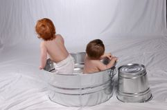 Twins not looking. Twin one-year-olds, not looking at camera for their picture, in wash tub Stock Photography