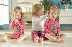 Twins and elder sister sitting at home royalty free stock images