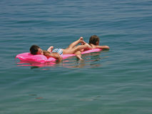 Twins with pink matrass on sea Stock Photos