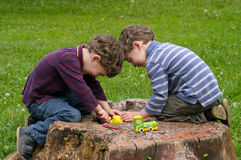 Twins play with animation. Identical twins sit on the stump of the tree and play with animation. They are laughing. They dressed in stripy shirts and trousers Royalty Free Stock Photography