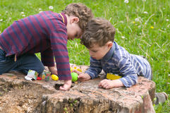 Twins play with concentration. Identical twins sit on the stump of the tree and play with concentration. They are attentive and lean head to head. They dressed Stock Images