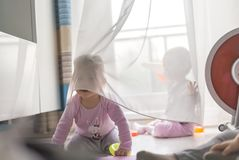 Twins play with a curtain. At home on the floor, in front of the balcony window Stock Photo