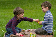 Twins play with enthusiasm. Identical twins sit on the stump of the tree and play with interest. They are laughing. One brother seize the toy from another. They stock photos