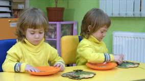 Twins play in a logical toy. Four-year-old children in the classroom for intellectual development medium shot stock video footage